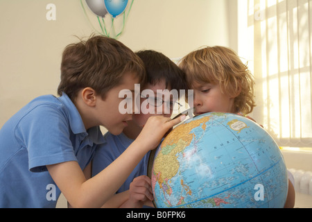 Boys looking at an earth globe - Stock Photo