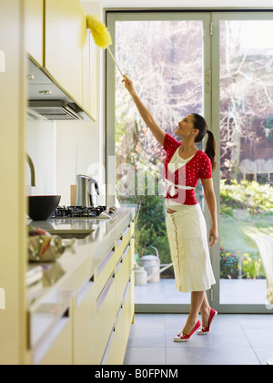Young woman dusting in kitchen - Stock Photo