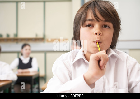 Boy with pencil in mouth, in classroom - Stock Photo