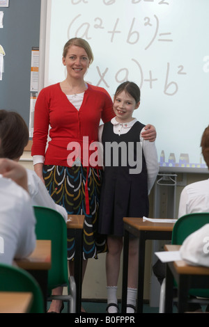 Teacher and girl in front of whiteboard - Stock Photo