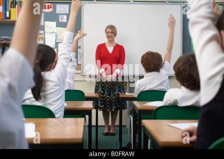 Children raising hands in classroom - Stock Photo