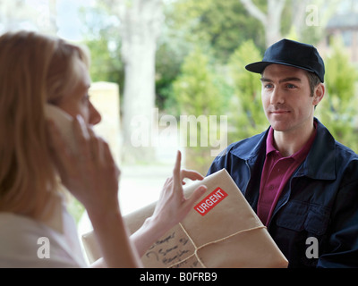 Woman on phone, courier in doorway - Stock Photo