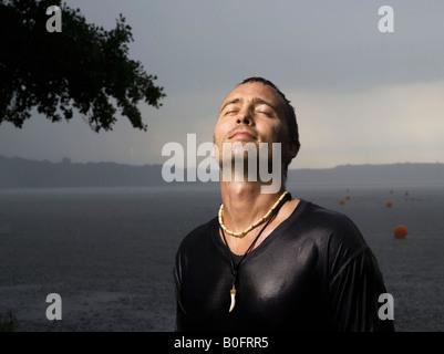 Man standing in rain, eyes closed - Stock Photo