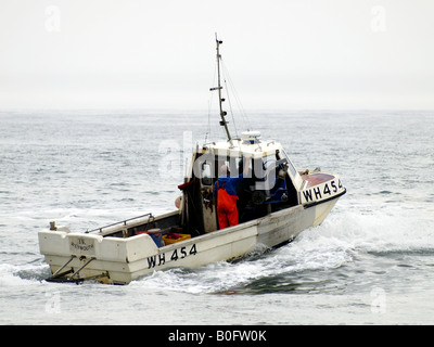 Fishing boat and crew heading out to sea on a grey day - Stock Photo