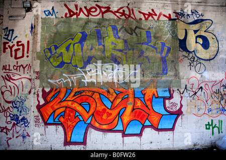 Wall covered in colourful graffiti Generic city landscape - Stock Photo