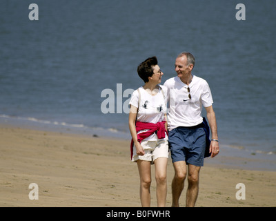 Middle aged couple walking along the seaside, looking lovingly into each others eyes. - Stock Photo