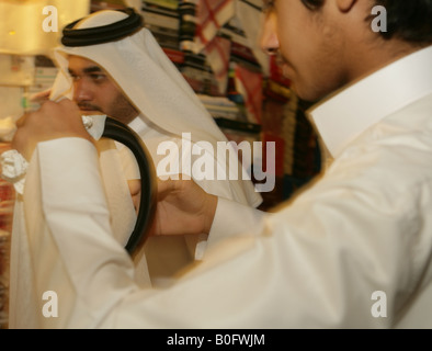 Men trying on traditional headdress at the Souq Waqif market in Doha, Qatar. - Stock Photo