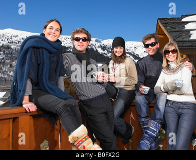 Group of friends on terrace at mountains - Stock Photo