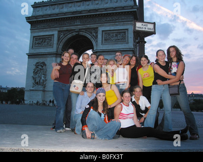 snap shot of school group posing in front of Arc de Triomphe Paris France at dusk - Stock Photo
