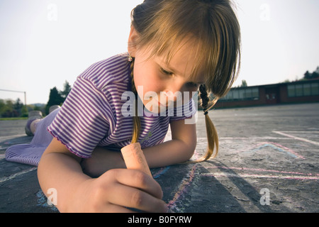 Young girl laying down on pavement drawing with chalk. - Stock Photo