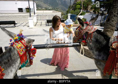 Mother and toddler looking at the donkey taxis, Mijas Pueblo, Costa del Sol, Andalucia, Spain - Stock Photo