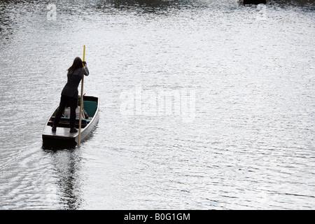 A girl punts a boat along the river Cam, Cambridge England - Stock Photo
