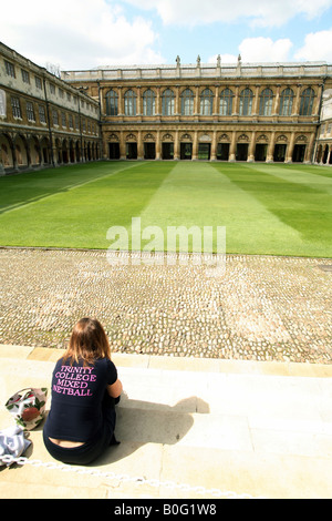 A Student sits in Nevile's Court facing the Wren library, Trinity College Cambridge England - Stock Photo