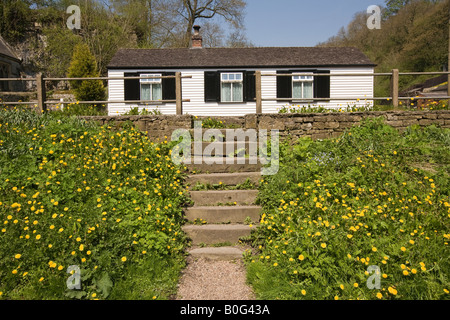 White Painted Country Cottage With Wild Flowers Growing