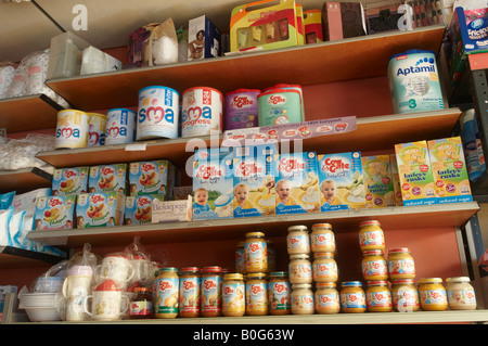 Baby food, powdered milk, and gift sets on shelves in pharmacy chemist shop - Stock Photo