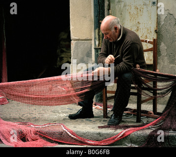 Old fisherman repairing his nets Cefalu Sicily Italy EU. - Stock Photo