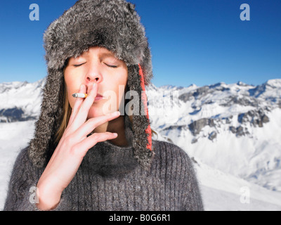 Young woman in hat smoking - Stock Photo