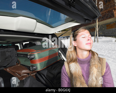 Young woman in front of packed car - Stock Photo