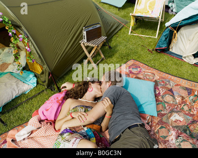Woman and man laying kissing on blanket - Stock Photo
