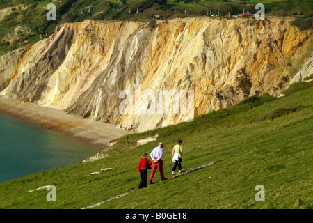 Tourists Walking on Coastal Path and the Coloured Sand Cliffs at Alum Bay Isle of Wight England - Stock Photo