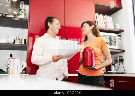 Couple discuss paperwork in kitchen - Stock Photo