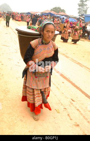 flower hmong women leaving bac ha market after selling firewood - Stock Photo
