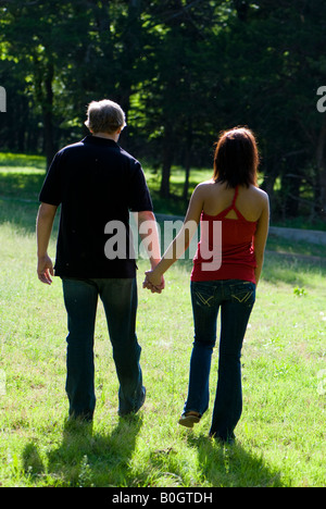 A young couple hold hands and walk in the countryside, backlit by the sunshine. Oklahoma, USA. - Stock Photo