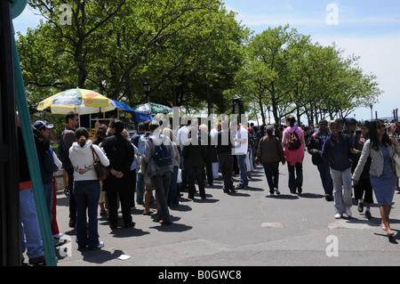 On a Sunday in Lower Manhattan a long line of people waits to board the ferry for the Statue of Liberty and Ellis - Stock Photo