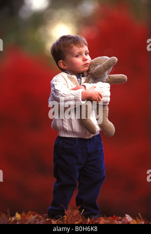 A three year old boy clutches his stuffed bunny to his chest on an autumn day with new fallen leaves - Stock Photo