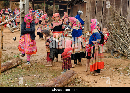 Flower Hmong, Mong, or Miao women and children in traditional dress at a market, Ha Giang Province, North Vietnam - Stock Photo