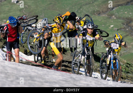 Mountain bikers pushing and carrying their bikes through the snow during the Transalp Challenge at Pfunderer Joch, - Stock Photo