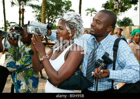 Photographer showing woman how to operate a video camera, Douala, Cameroon, Africa - Stock Photo
