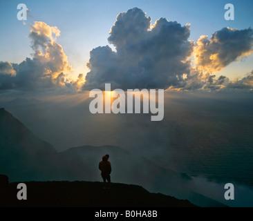 Peak of Stromboli Volcano, man standing in backlight, sunbeams, rays of sunlight, Aeolian Islands, Sicily, Italy - Stock Photo