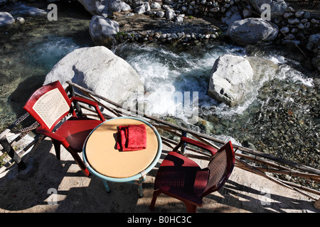 Two red chairs and a table at a restaurant patio overlooking mountain rapids, Ourika Valley, High Atlas Range, Morocco, - Stock Photo