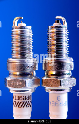 Comparison of iridium spark plug and standard spark plug - Stock Photo