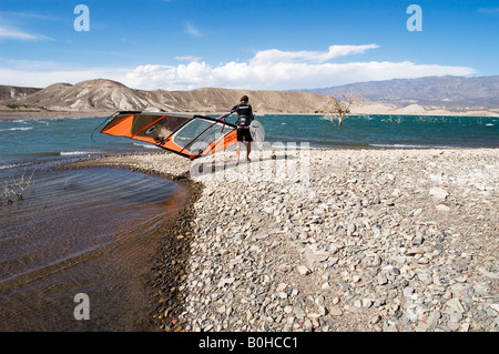 Windsurfer in wetsuit carrying his board and sail across the arid gravel windswept lake shore surrounded by mountains, - Stock Photo