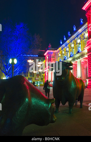 The Bull and Bear statue in front of the brightly lit Frankfurt Stock Exchange at night, illuminated by multicoloured - Stock Photo