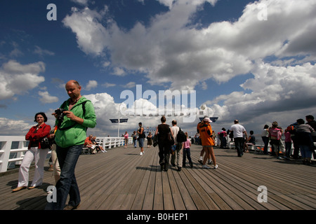 Tourist walking over a wooden bridge in Sopot, Baltic Sea coast, Poland - Stock Photo