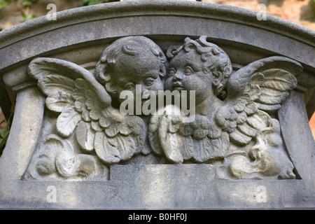 Stone putti, cherubs on a gravestone, Alter Suedfriedhof, old cemetery in Munich, Bavaria, Germany - Stock Photo