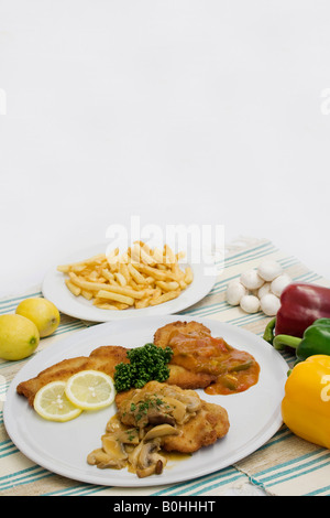 Wiener schnitzel served on a white plate surrounded by a green, red and yellow peppers, mushrooms, lemons and a - Stock Photo