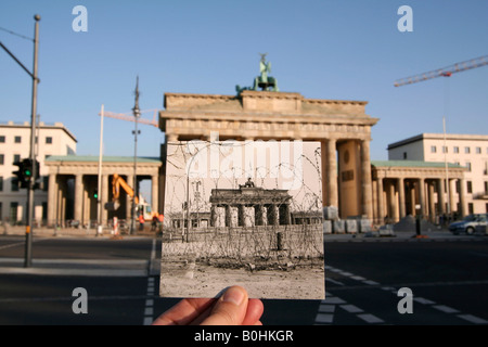 Then and now, hand holding an old black and white photo of Brandenburger Tor or Brandenburg Gate showing the Berlin - Stock Photo
