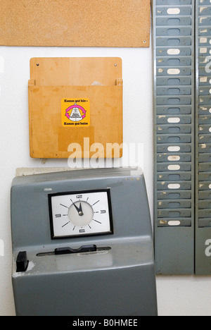 Tilted attendance recorder (time punch clock) showing five minutes to twelve o'clock, 5 to 12, next to an empty - Stock Photo
