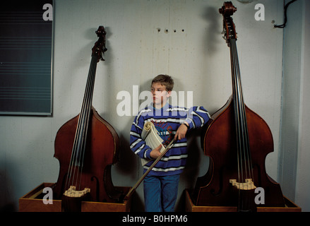 A boy standing between two double basses as he waits for his music lesson, Luxembourg. - Stock Photo
