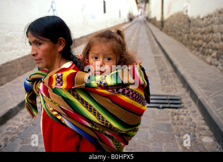 A woman carrying her daughter on her back in the street, Cuzco, Peru. - Stock Photo