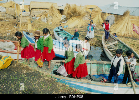 School children travelling home by boat on Lake Titicaca, Uros Islands, Peru. - Stock Photo
