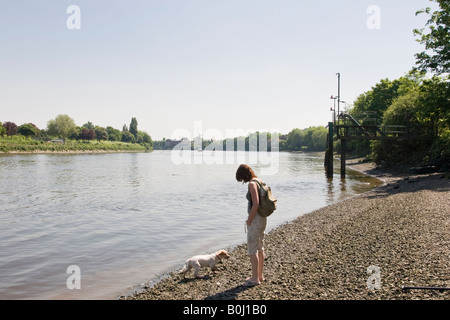 Young woman and dog by the side of the Thames at Mortlake - Stock Photo