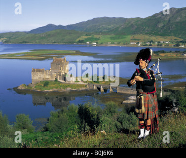 Scottish Bagpiper on hill above Eilean Donan Castle Scotland - Stock Photo