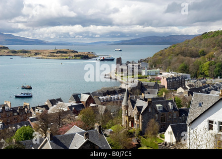View over Oban, towards Mull, with the Cathedral shown near the ferry boat - Stock Photo