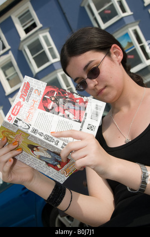 Young woman reading a Japanese manga graphic novel outdoors - Stock Photo