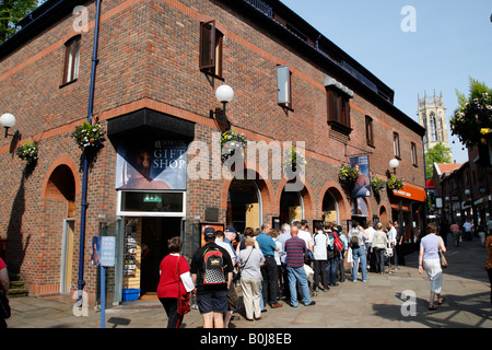 tourists queuing to enter the jorvik viking centre sign coppergate shopping centre york north yorkshire england - Stock Photo
